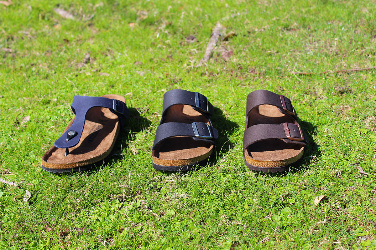 three brown sandals on green grass microfiber material